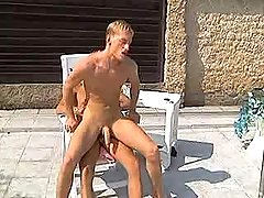 Two young golden-haired stallions lick booties and fuck by pool